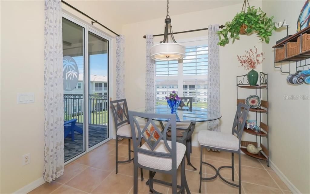 Generous dining area adjacent to lanai and plantation shutters on window overlooking pond. - Condo for sale at 200 San Lino Cir #233, Venice, FL 34292 - MLS Number is A4440138