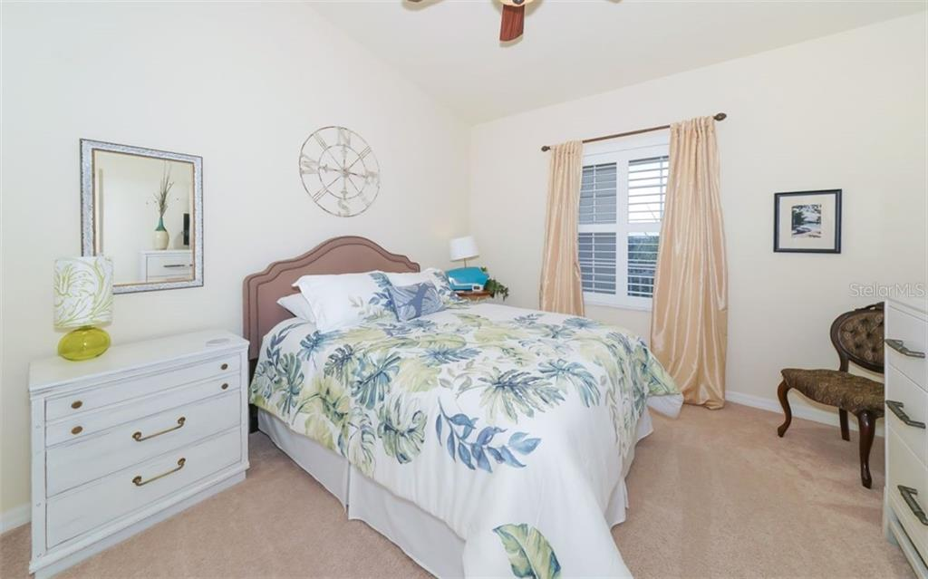 Guest bedroom with volume ceiling and plantation shutters. - Condo for sale at 200 San Lino Cir #233, Venice, FL 34292 - MLS Number is A4440138