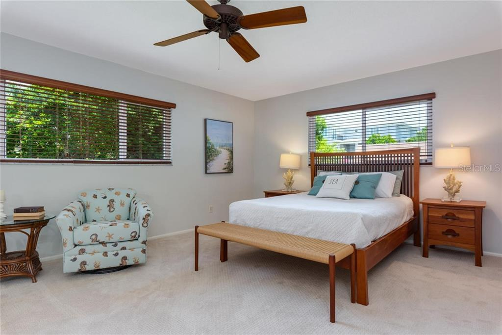 The enclosed Florida room. A perfect spot for a good book while watching the dolphins or sea birds out your window. - Single Family Home for sale at 701 Norton St, Longboat Key, FL 34228 - MLS Number is A4440596