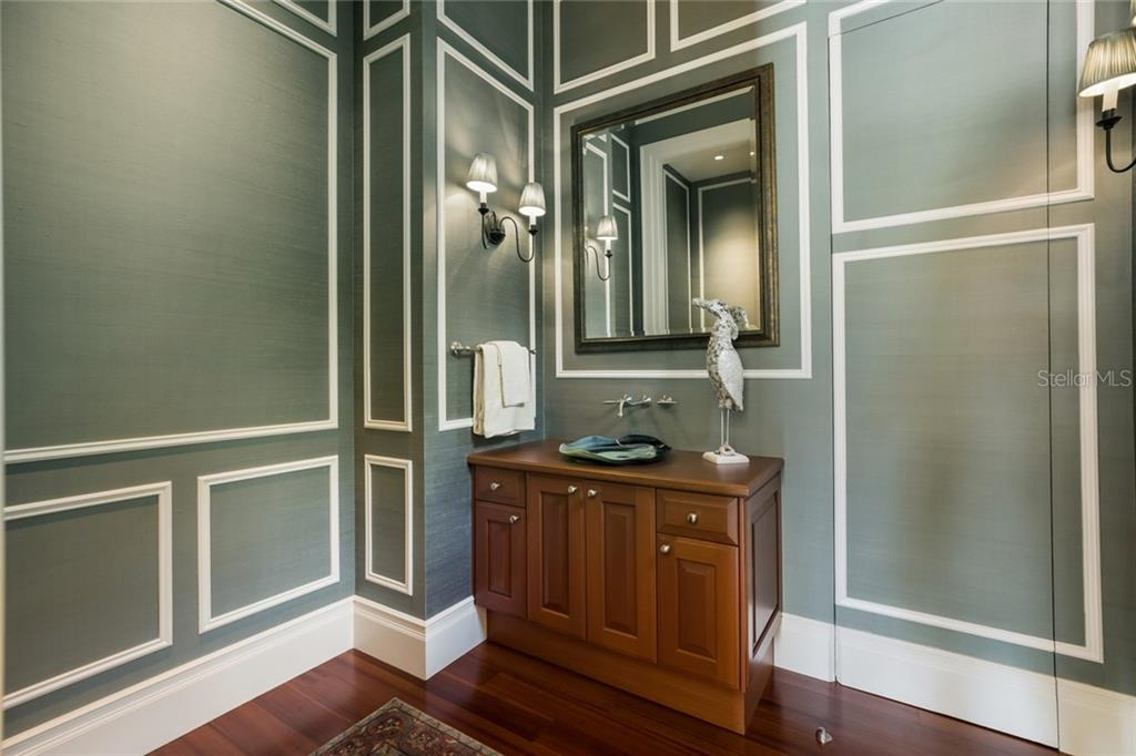 Exquisite powder room, featuring silk wall treatments and picture frame molding.  It is located off of great-room and boasts a hidden linen closet. - Single Family Home for sale at 1522 N Lake Shore Dr, Sarasota, FL 34231 - MLS Number is A4442286