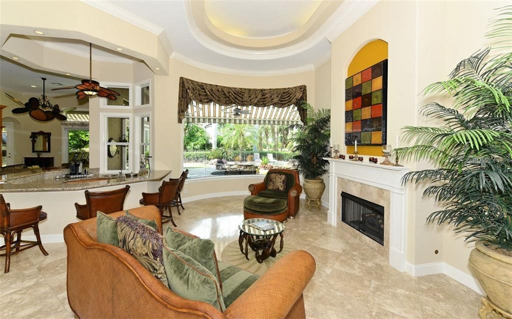 Formal living area with nearby central bar for entertaining and view of the outdoors beyond. - Single Family Home for sale at 586 N Macewen Dr, Osprey, FL 34229 - MLS Number is A4451482