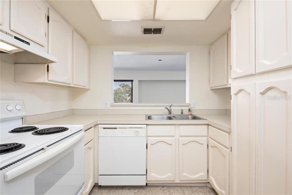 Kitchen with Pass Through Window to Dining Area - Condo for sale at 2731 Orchid Oaks Dr #301, Sarasota, FL 34239 - MLS Number is A4452031