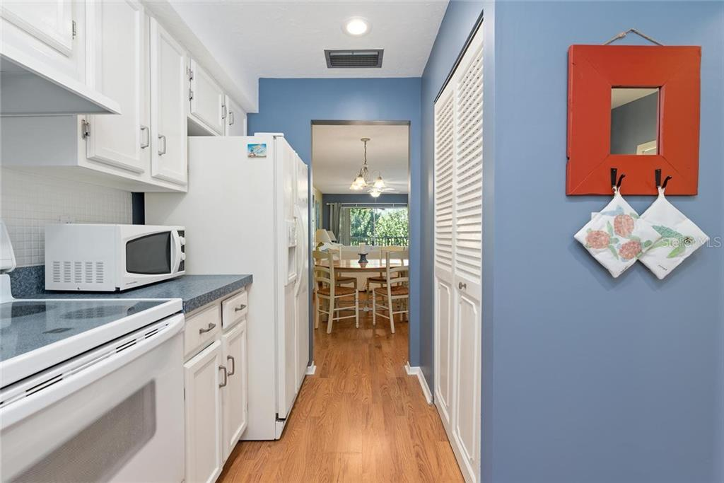 Looking through the kitchen into the living/dining area and out to the pool. In unit laundry is located in this kitchen closet. - Condo for sale at 4307 Gulf Dr #209, Holmes Beach, FL 34217 - MLS Number is A4452656