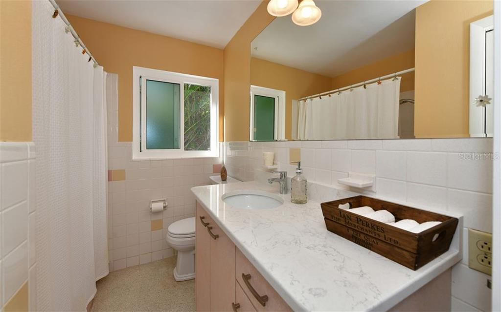 Third bathroom accessible from hallway downstairs with shower/tub combo - Single Family Home for sale at 623 Avenida Del Norte, Sarasota, FL 34242 - MLS Number is A4454692