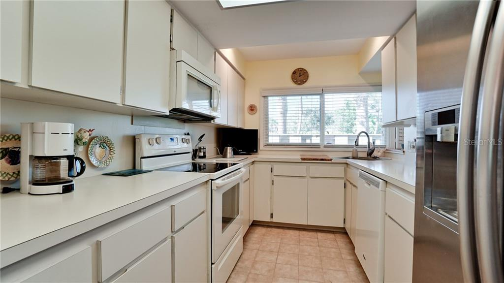 CUPBOARDS & KITCHEN CABINETS GALORE IN THIS COOK'S DELIGHT KITCHEN!  LARGE STAINLESS DOUBLE DOOR FRIDGE. PEAK OF THE GULF FROM KITCHEN WINDOW. - Condo for sale at 6700 Gulf Of Mexico Dr #116, Longboat Key, FL 34228 - MLS Number is A4456442