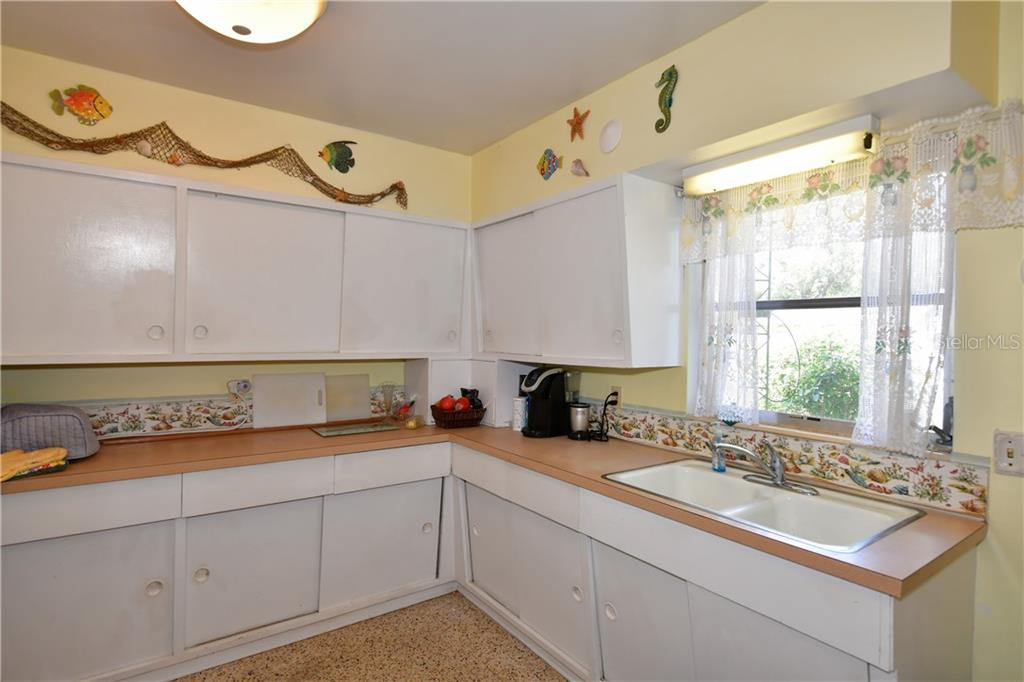 'Old Florida Kitchen' with with sliding doors and terrazzo - Single Family Home for sale at 2703 Trinidad St, Sarasota, FL 34231 - MLS Number is A4460680