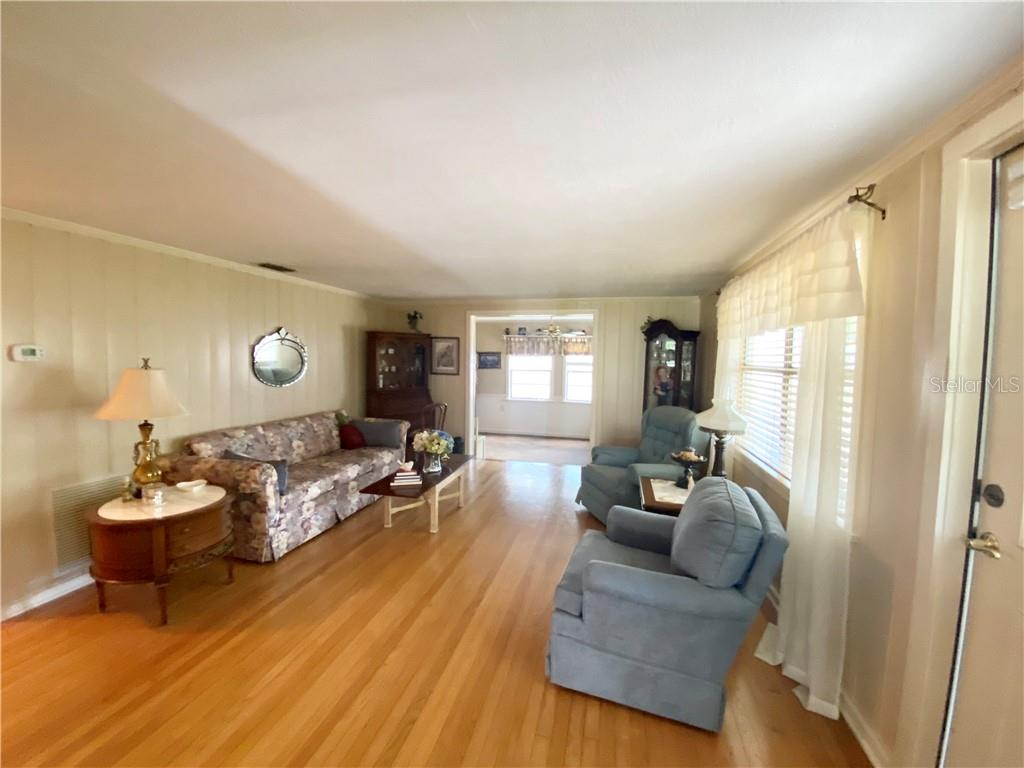 Living room, view to the Florida Room.  Door to the right exits to the Lanai. - Single Family Home for sale at 4300 Eastern Pkwy, Sarasota, FL 34233 - MLS Number is A4464200