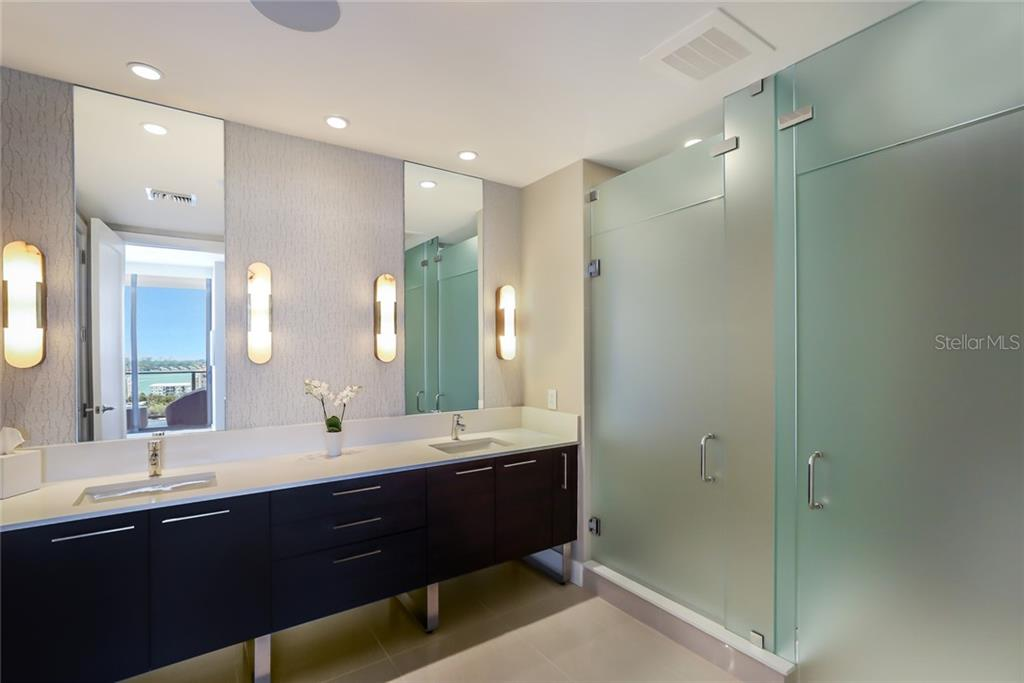 The master bath has been customized with glamorous sconces and additional drawer space. - Condo for sale at 1155 N Gulfstream Ave #1404, Sarasota, FL 34236 - MLS Number is A4467921