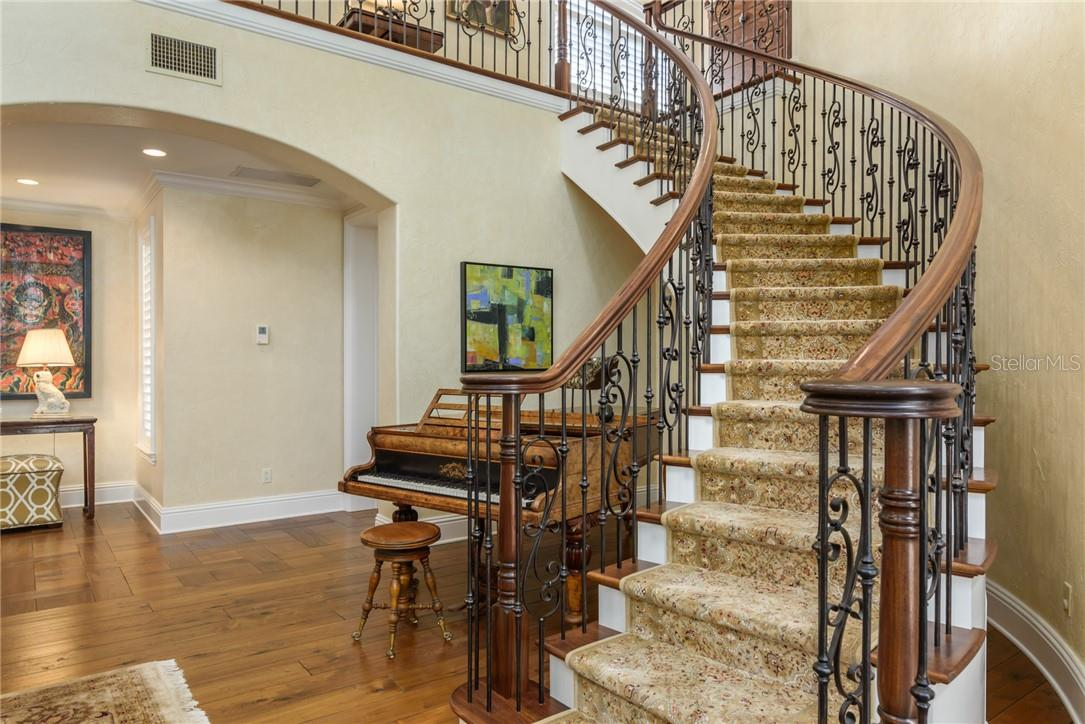 Dramatic winding staircase with wrought iron metalwork and stained handrails with custom carpeting anchors the two story living room. - Single Family Home for sale at 1807 Oleander St, Sarasota, FL 34239 - MLS Number is A4475067
