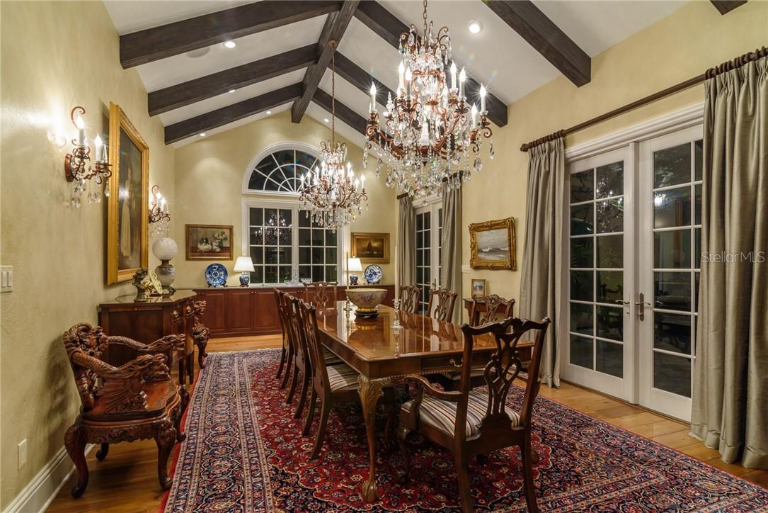 This beamed dining space welcomes a large or small crowd with views over the poolscape via French doors with silk draperies. - Single Family Home for sale at 1807 Oleander St, Sarasota, FL 34239 - MLS Number is A4475067