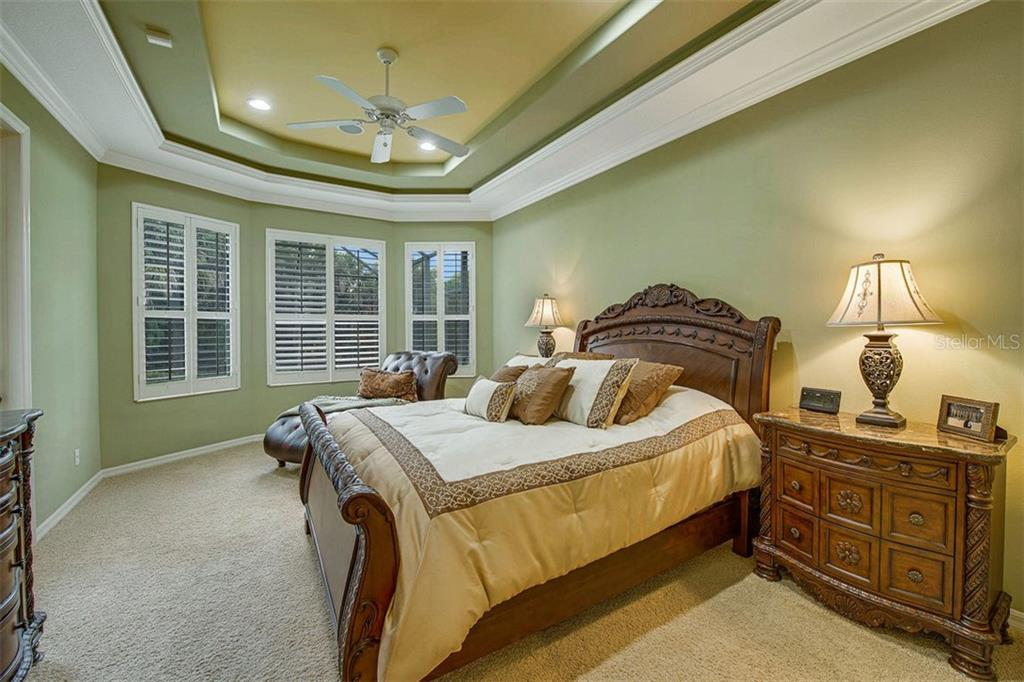 Owners suite with tray ceiling, crown molding,  plantation shutters, sitting area, and pool/lanai access. - Single Family Home for sale at 684 Crane Prairie Way, Osprey, FL 34229 - MLS Number is A4478575