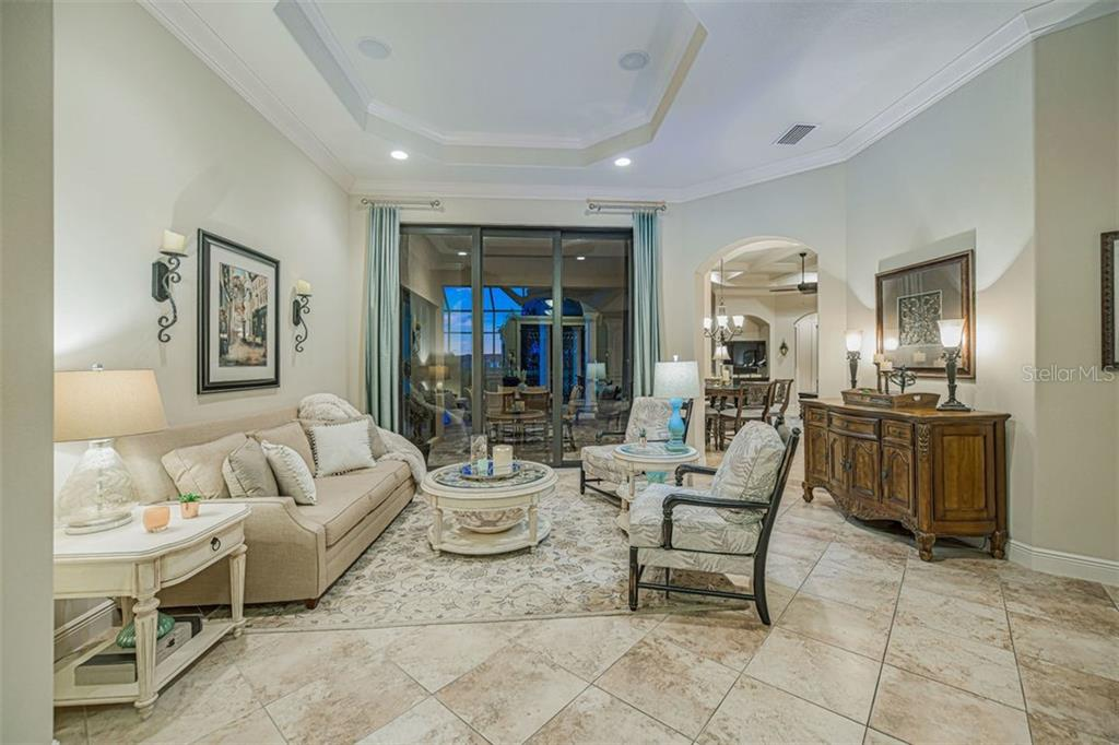 Formal living room with lake views and sliders to the lanai - Single Family Home for sale at 14507 Leopard Crk, Lakewood Ranch, FL 34202 - MLS Number is A4478709