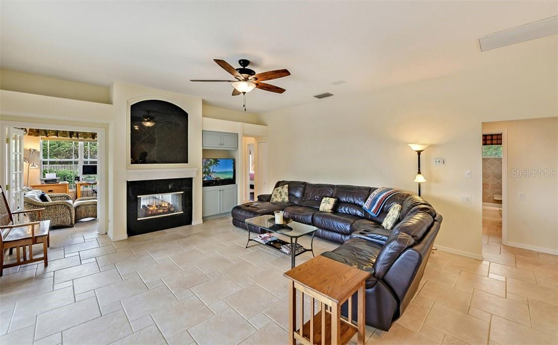 Family room with gas fireplace - two-sided to Florida Room (used as a 2nd office) - Single Family Home for sale at 7832 Panther Ridge Trl, Bradenton, FL 34202 - MLS Number is A4483837