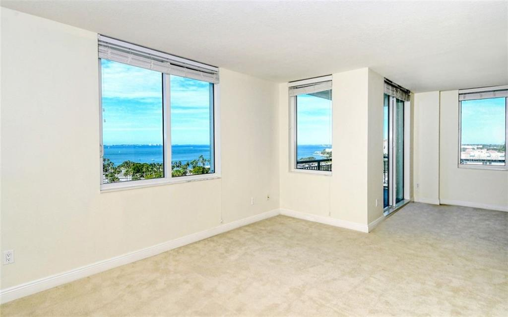 Living room looking towards the kitchen; door leads to a bedroom - Condo for sale at 800 N Tamiami Trl #1007, Sarasota, FL 34236 - MLS Number is A4485565