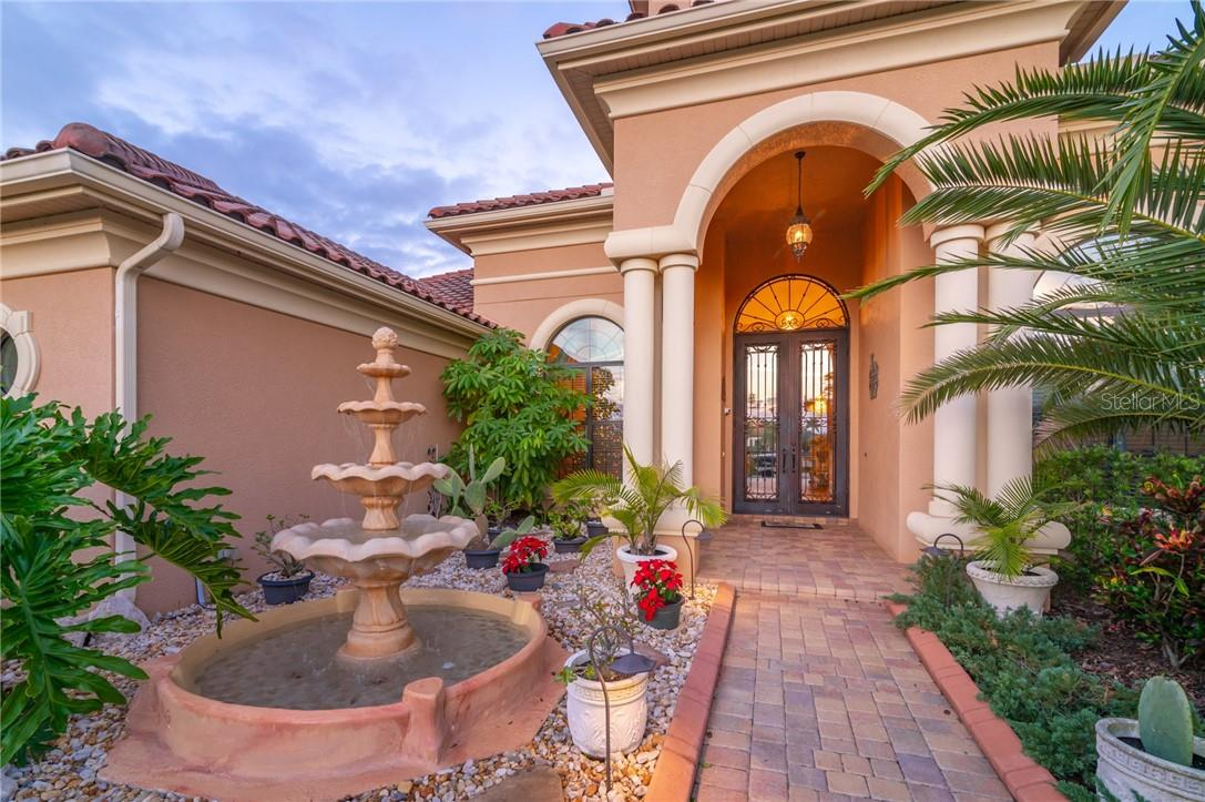 You will find yourself entering through a tropical setting with plants and a fountain along the path to the front door. - Single Family Home for sale at 11720 Rive Isle Run, Parrish, FL 34219 - MLS Number is A4486302