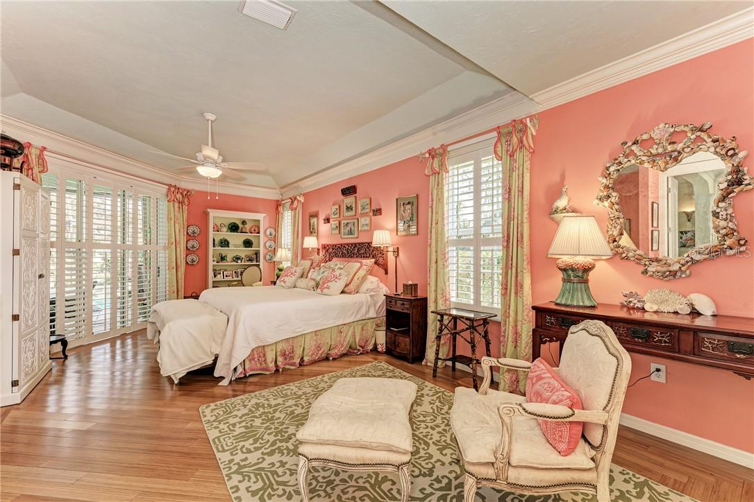 Master suite with coffered ceilings with additional lighting, ceiling fan, plantation shutters, and beautiful wood floors - Single Family Home for sale at 7879 Estancia Way, Sarasota, FL 34238 - MLS Number is A4490318