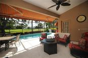 Covered lanai and swimming pool with golf course views - Villa for sale at 7707 Calle Facil, Sarasota, FL 34238 - MLS Number is A4191635