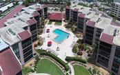Community swimming pool and paver brick sun deck - Condo for sale at 6480 Midnight Pass Rd #217, Sarasota, FL 34242 - MLS Number is A4202790