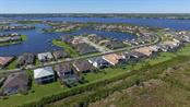 Aerial over Tidewater Preserve - property is 2nd to left of cul-de-sac, white with double porches/lanais - Single Family Home for sale at 5504 Tidewater Preserve Blvd, Bradenton, FL 34208 - MLS Number is A4429479