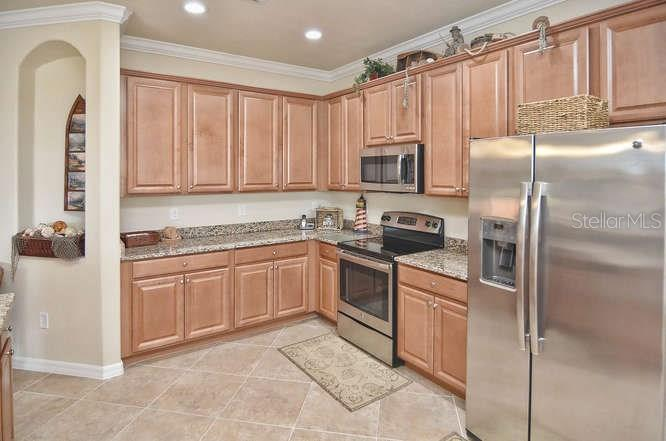 View of Kitchen showing beautiful wood cabinets and stainless appliances - Single Family Home for sale at 13210 Amerigo Ln, Venice, FL 34293 - MLS Number is N5913012