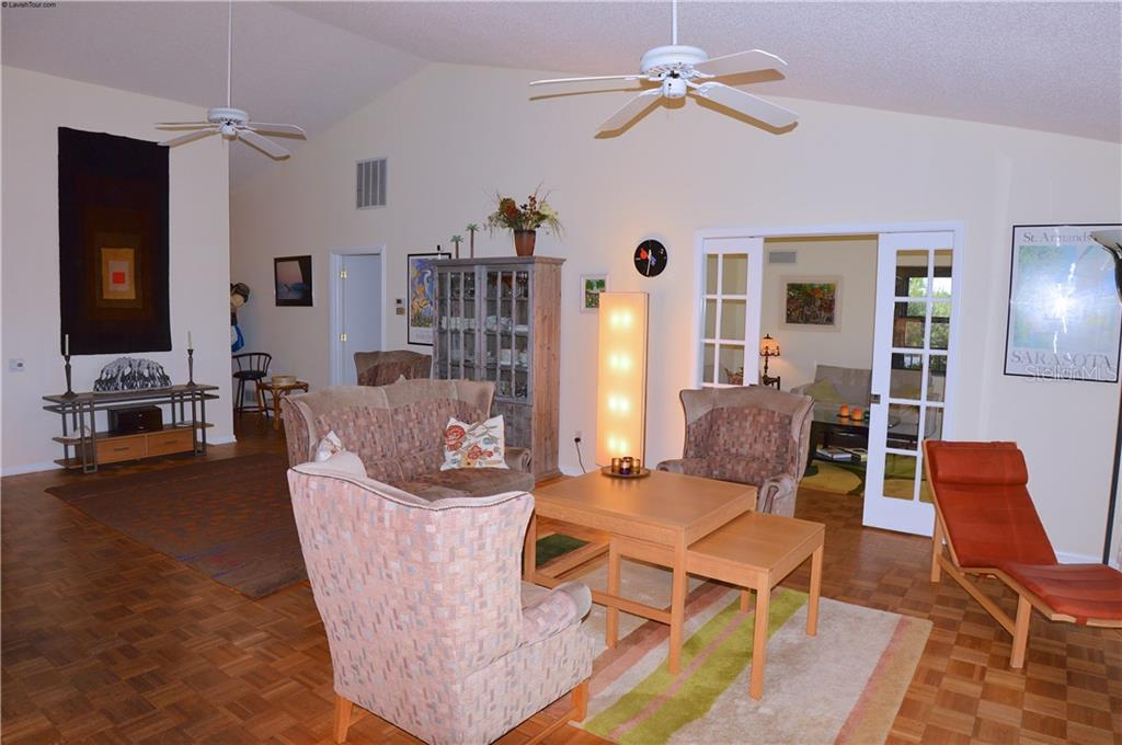 Living room with French door to den - Single Family Home for sale at 1649 Manor Rd, Englewood, FL 34223 - MLS Number is N5914466