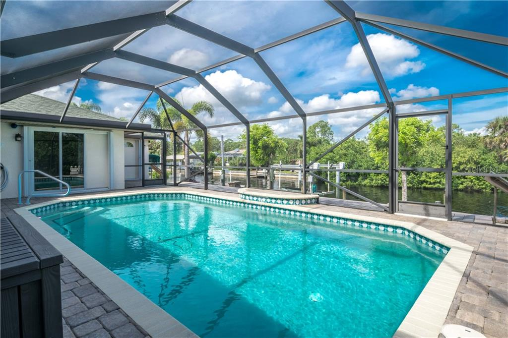 Heated Screened Pool with relaxing Water Fall feature beautiful Paver deck and Lanai plus both Water and Electric within the pool cage. The pool Heater 2 yrs old.The Walkway along the back of the pool outside the screen cage sits on top of a stem wall - Single Family Home for sale at 5149 Latham Ter, Port Charlotte, FL 33981 - MLS Number is N5914515
