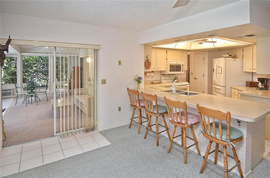 Breakfast bar/dining room with sliders to Florida room - Single Family Home for sale at 1410 Strada D Argento, Venice, FL 34292 - MLS Number is N5914540