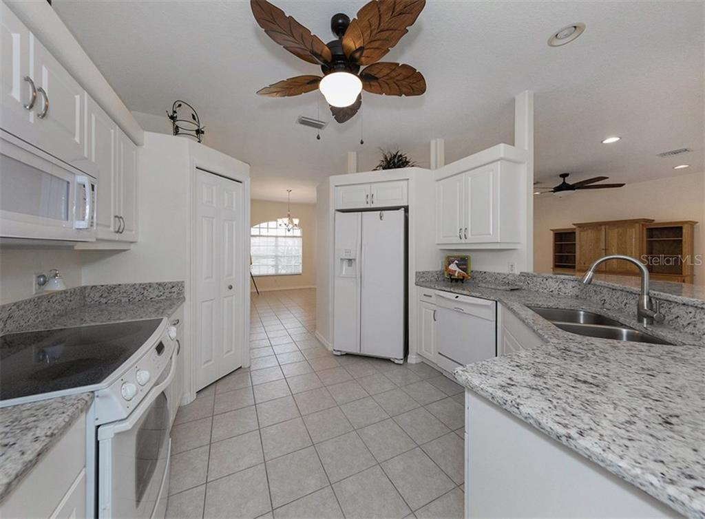 Kitchen to dining room - Single Family Home for sale at 2196 Calusa Lakes Blvd, Nokomis, FL 34275 - MLS Number is N5915879