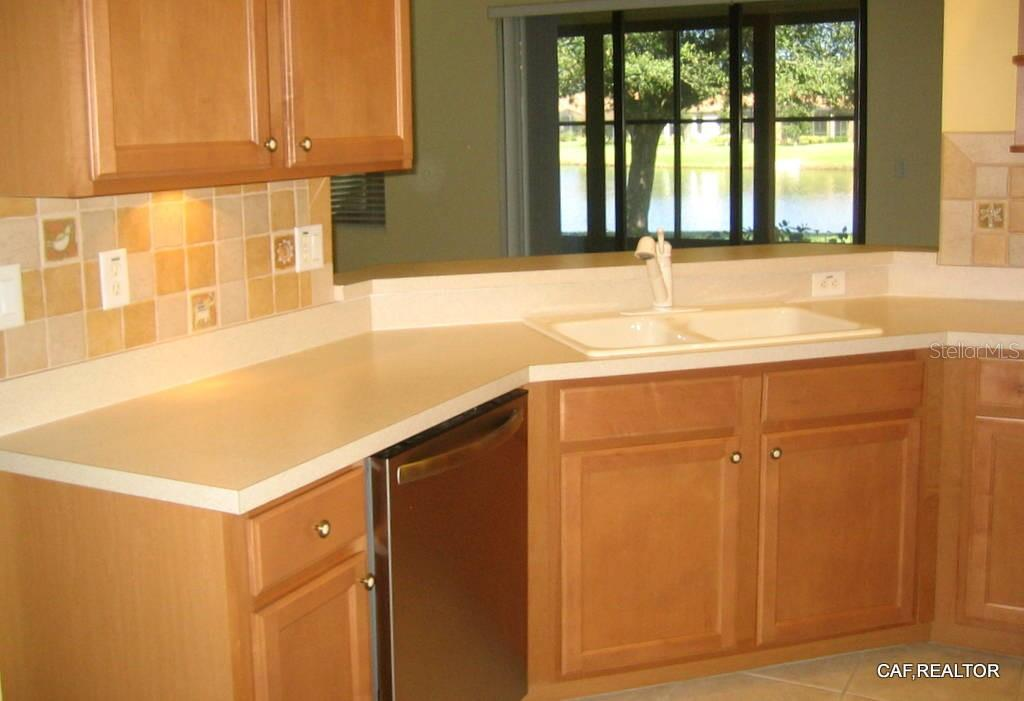 Lake view from Kitchen sink - Villa for sale at 1445 Maseno Dr, Venice, FL 34292 - MLS Number is N5916837