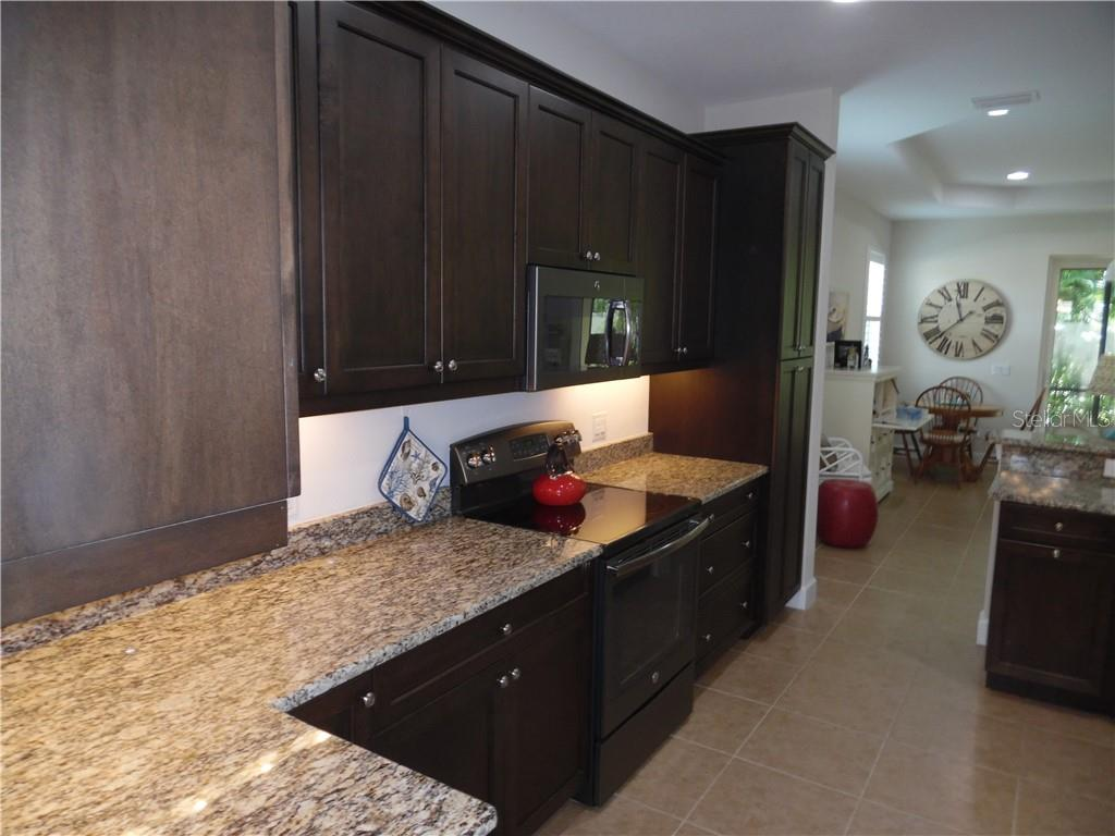 kitchen cabinets, stove, and microwave oven - Single Family Home for sale at 239 Nolen Dr, Venice, FL 34292 - MLS Number is N6101457