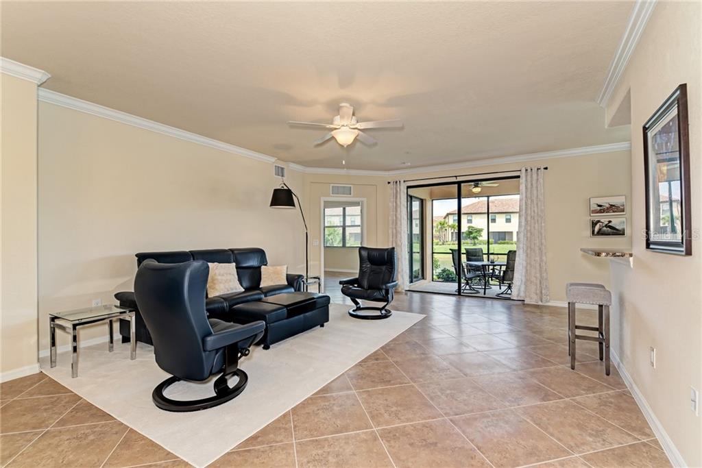 Living room and sliders to lanai. - Condo for sale at 20200 Ragazza Cir #102, Venice, FL 34293 - MLS Number is N6101798