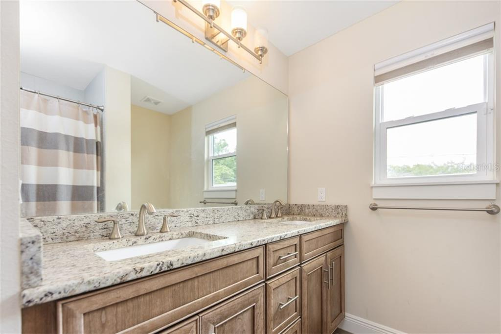 Upstairs bath room has dual sinks, granite counter tops and shower with tub. - Single Family Home for sale at 1716 Arlington St, Sarasota, FL 34239 - MLS Number is N6104891