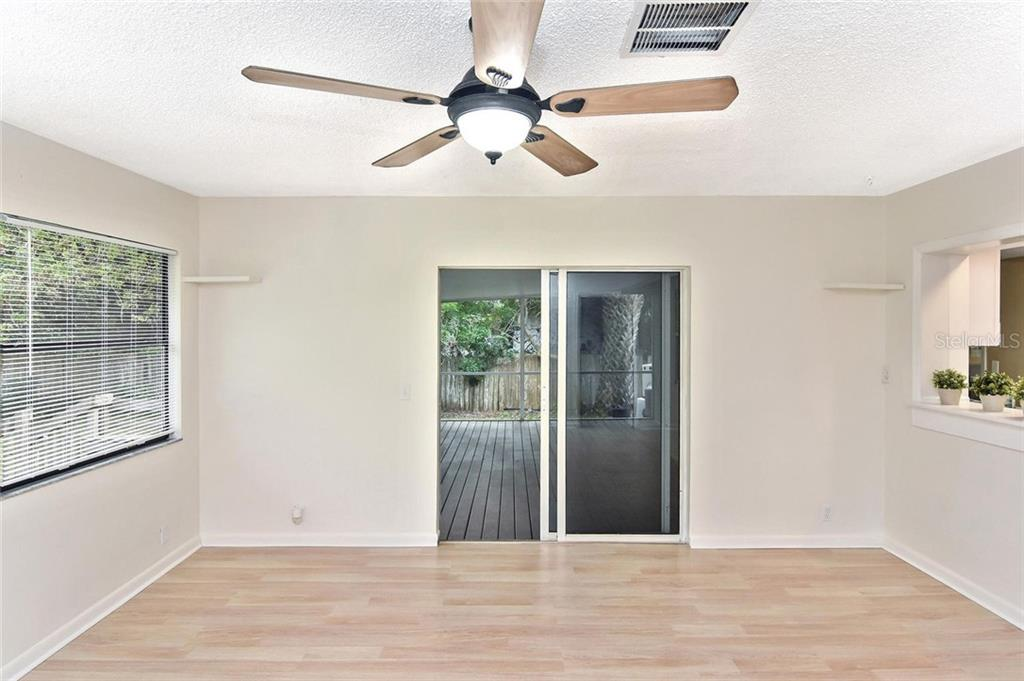 Family room with sliding doors to covered screened-in porch. - Single Family Home for sale at 5681 Hale Rd, Venice, FL 34293 - MLS Number is N6107822