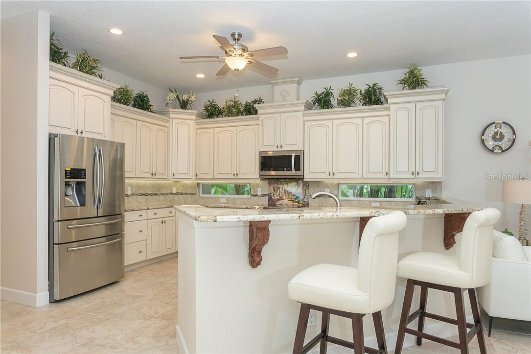 Open kitchen with stainless applianced & granite countertops. - Single Family Home for sale at 1670 Maria St, Englewood, FL 34223 - MLS Number is N6113779