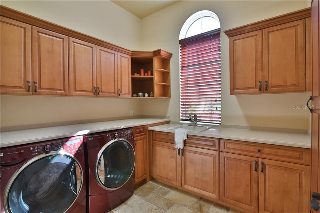 This fabulous well appointed laundry quarters with window to the front of the home provides tons of natural lighting.  Bright and cheery!  Solid cabinetry and built-in iron center. - Single Family Home for sale at 8365 Catamaran Cir, Lakewood Ranch, FL 34202 - MLS Number is A4187448