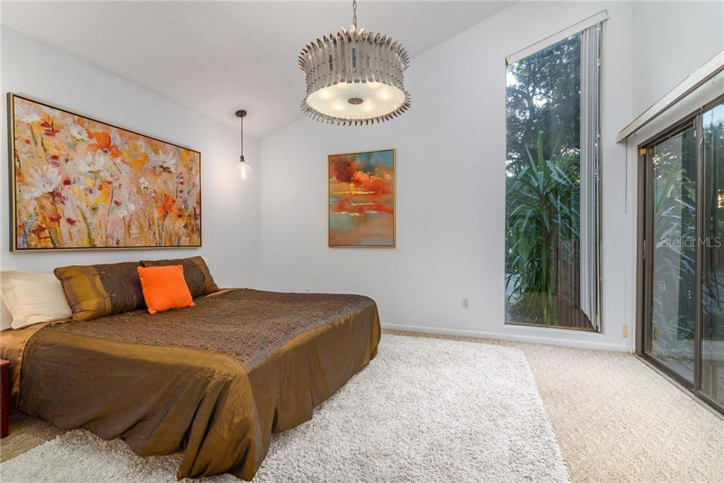 Bedroom with Vaulted ceilings, Sliders to front deck and large walk in closet - 14' x 12' - Single Family Home for sale at 5303 Hidden Harbor Rd, Sarasota, FL 34242 - MLS Number is A4421223