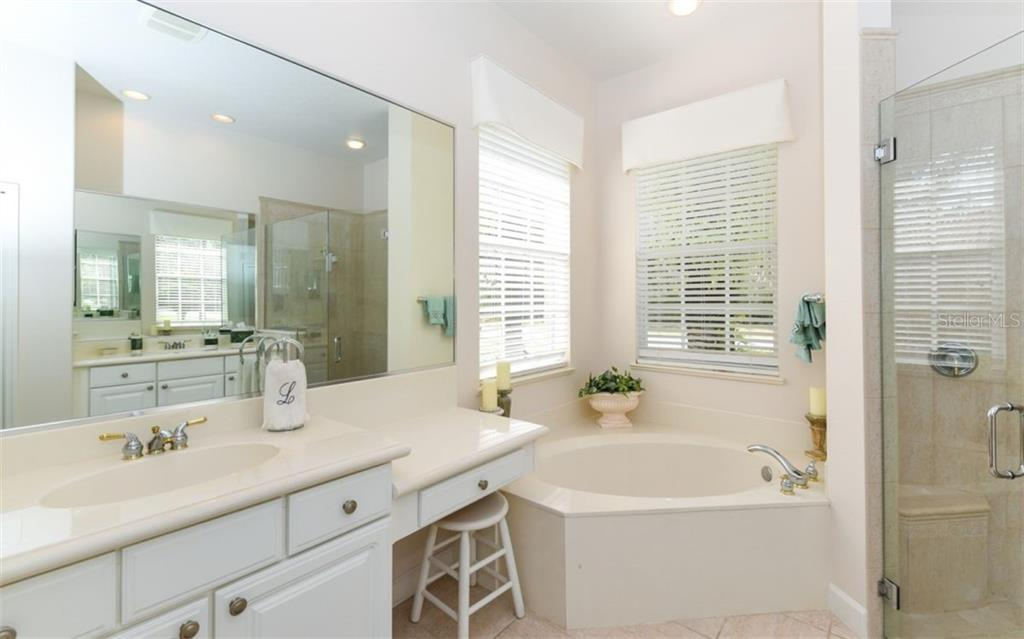 Master bath with separate vanities, deep soaking tub and frameless glass shower doors! - Single Family Home for sale at 8473 Eagle Preserve Way, Sarasota, FL 34241 - MLS Number is A4425945