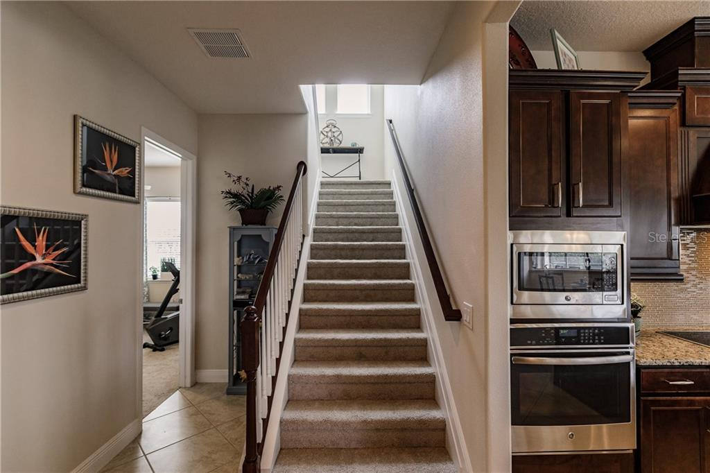 Stairs lead up to the guest quarters/bonus space. - Single Family Home for sale at 17006 1st Dr E, Bradenton, FL 34212 - MLS Number is A4432830