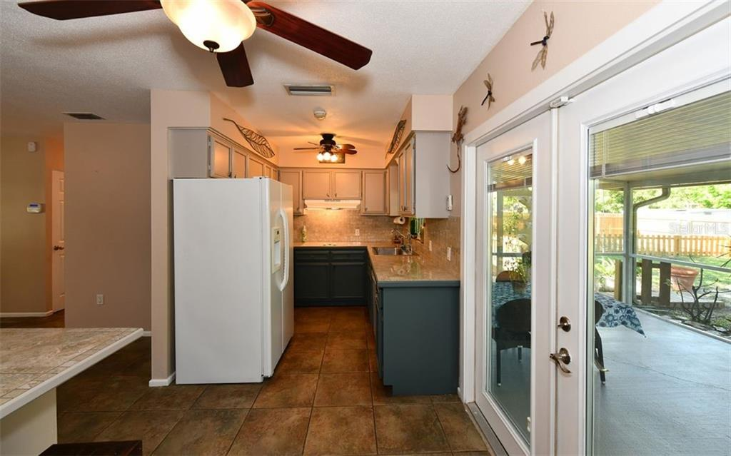 Kitchen & doors to the lanai which have interior shades. - Single Family Home for sale at 120 23rd Street Ct Ne, Bradenton, FL 34208 - MLS Number is A4438232
