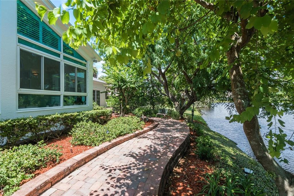 Gorgeous brick pavered lakeside walking path around the pool lanai and to the Guest Home while under the shade of the mature Floridian landscape! - Single Family Home for sale at 3702 Beneva Oaks Blvd, Sarasota, FL 34238 - MLS Number is A4438878