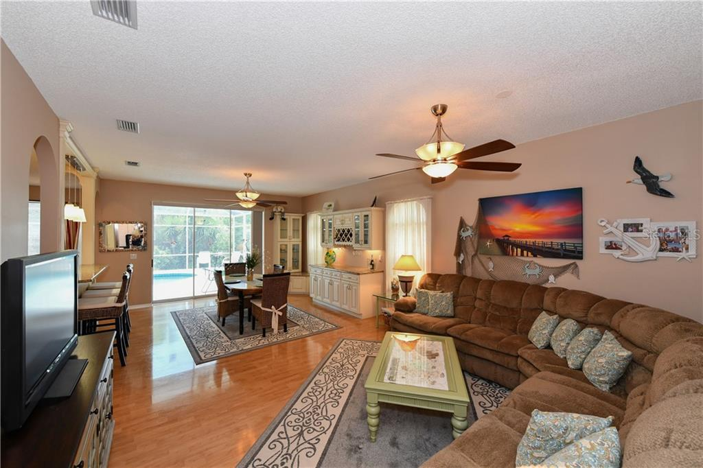 Open living to the dining with views of the pool and Lanai area.  Notice the built in cabinetry in Dining area...  matching kitchen cabinetry and granite countertops. - Single Family Home for sale at 4074 Via Mirada, Sarasota, FL 34238 - MLS Number is A4439141